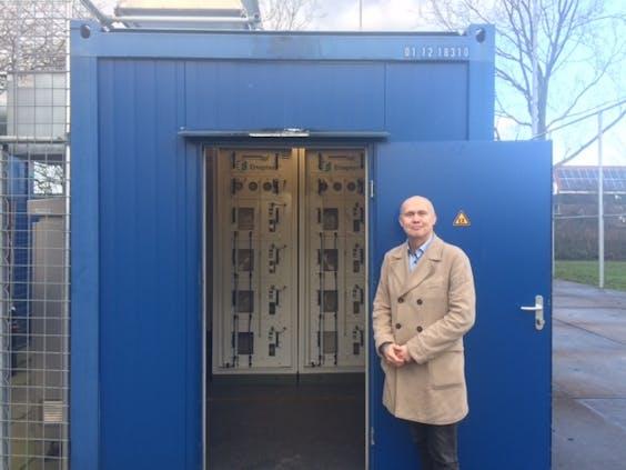 Albert van der Molen (waterstofexpert Stedin) staat voor de elektrolysers die zonne-energie van het dak omzetten in waterstof.